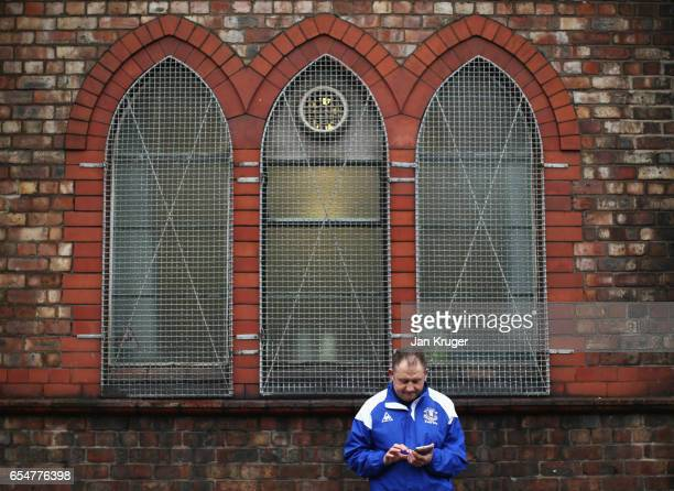 A fan waits outside the stadium prior to the Premier League match between Everton and Hull City at Goodison Park on March 18 2017 in Liverpool England