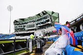 A fan waits patiently in the rain for the start of play on day one of the 2nd Investec Test Match between England and New Zealand at Headingley on...