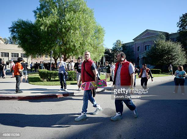 A fan walks around with 'Back To The Future' hoverboard in the Hill Valley Courthouse square in the back lot of Universal Studios during 'Back To The...