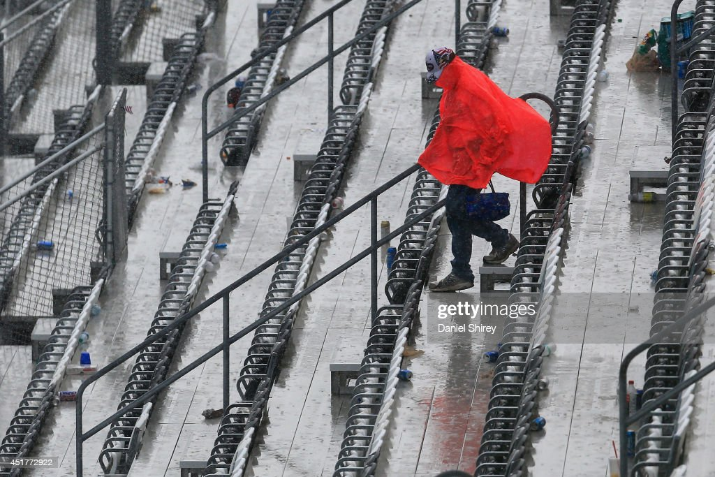 A fan walks out of the grandstand in the rain after the NASCAR Sprint Cup Series Coke Zero 400 at Daytona International Speedway on July 6, 2014 in Daytona Beach, Florida.