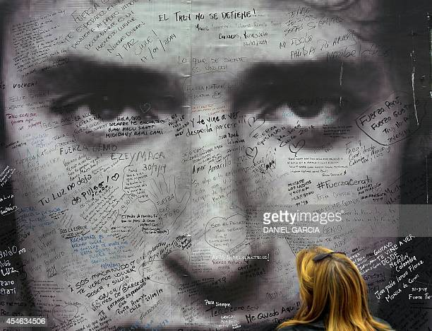 A fan watches a poster of Argentine artist Gustavo Cerati in front of the clinic where the musician died from a stroke on September 4 2014 in Buenos...