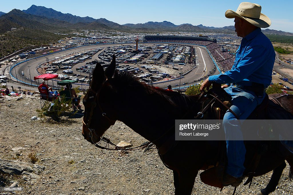 A fan watches cars race as he rides a horse during the NASCAR Sprint Cup Series CampingWorld.com 500 at Phoenix International Raceway on March 15, 2015 in Avondale, Arizona.