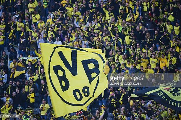A fan waves a Borussia Dortmund flag ahead of the German Cup DFB Pokal final football match between BVB Borussia Dortmund and VfL Wolfsburg in Berlin...
