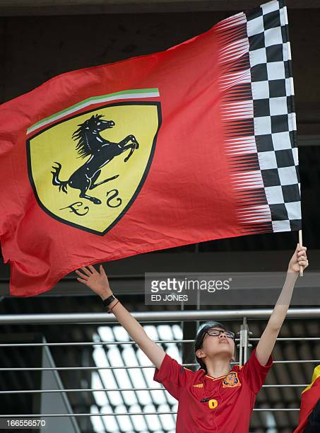 A fan waves a Ferarri flag prior to the start of the Formula One Chinese Grand Prix in Shanghai on April 14 2013 AFP PHOTO / Ed Jones