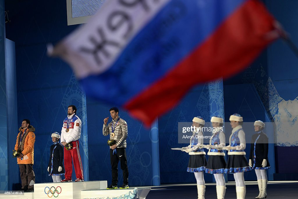 A fan waves a flag as gold medalist <a gi-track='captionPersonalityLinkClicked' href=/galleries/search?phrase=Alexander+Tretiakov&family=editorial&specificpeople=723551 ng-click='$event.stopPropagation()'>Alexander Tretiakov</a> of Russia stands on the podium with silver medalist <a gi-track='captionPersonalityLinkClicked' href=/galleries/search?phrase=Martins+Dukurs&family=editorial&specificpeople=4876286 ng-click='$event.stopPropagation()'>Martins Dukurs</a> of Latvia (left) and bronze medalist Matthew Antoine of the United States (right) watch the presentation during the medals ceremony for the men's skeleton. Sochi 2014 Winter Olympics on Sunday, February 16, 2014.