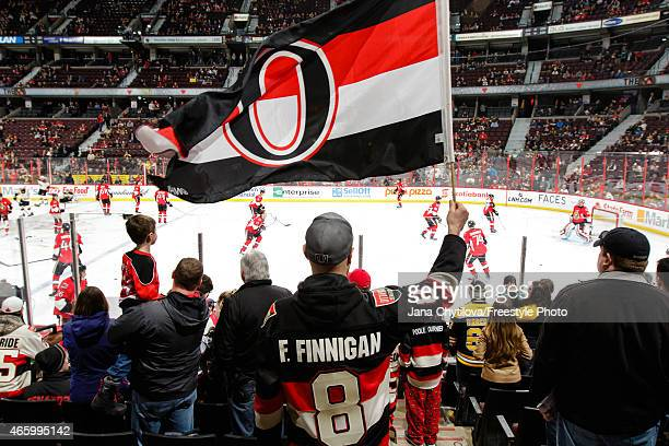 A fan waves a flag bearing the heritage logo of the Ottawa Senators during warmups prior to an NHL game against the Boston Bruins at Canadian Tire...
