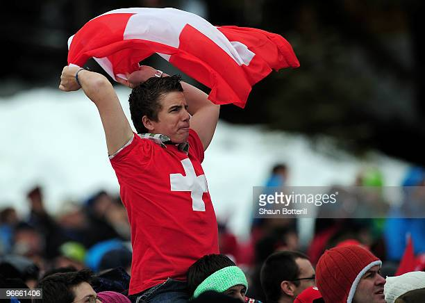 A fan waves a flag from Switzerland waves a flag as he cheers for Simon Ammann of Switzerland during the Ski Jumping Normal Hill Individual on day 2...
