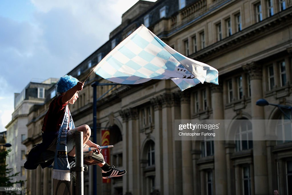 A fan waves a flag from the top of a street sign as Manchester City players parade the Barclays Premier League trophy in front of thousands of fans during their victory parade around the streets of Manchester on May 14, 2012 in Manchester, England.