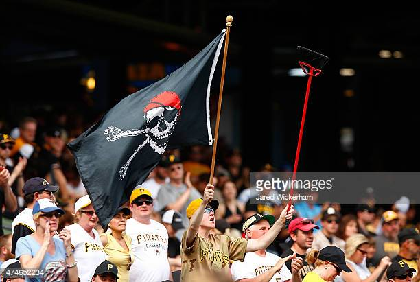 A fan waves a Pittsburgh Pirates flag and a broom following their 91 win and sweep of the series against the New York Mets during the game at PNC...