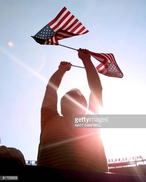 A fan waves American flags during a video tribute to New York City firefighters and police officers between innings of the baseball game between the...