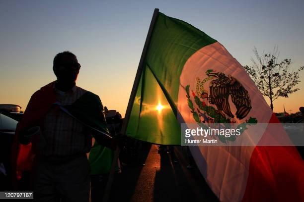 A fan waves the flag of Mexico in the parking lot before a game between Mexico and the United States at Lincoln Financial Field on August 10 2011 in...
