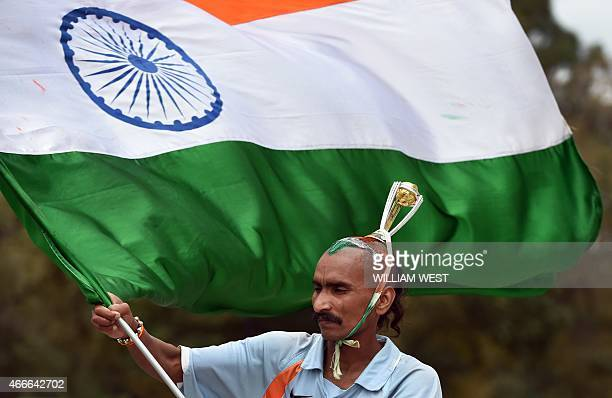 A fan waves the Indian national flag during the Indian cricket team's training session ahead of their 2015 Cricket World Cup quarterfinal match...