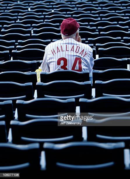 A fan wearing a Roy Halladay of the Philadelphia Phillies jersey watches batting practice before Game 2 of the NLDS against the Cincinnati Reds at...