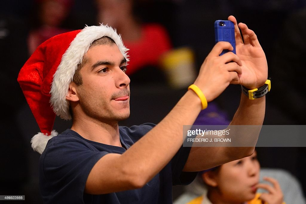 A fan wearing a Santa hat uses his cellphone to capture the players warming up ahead of the Los Angeles Lakers v Miami Heat Christmas Day matchup at Staples Center in Los Angeles, California on December 25, 2013. AFP PHOTO/Frederic J. BROWN