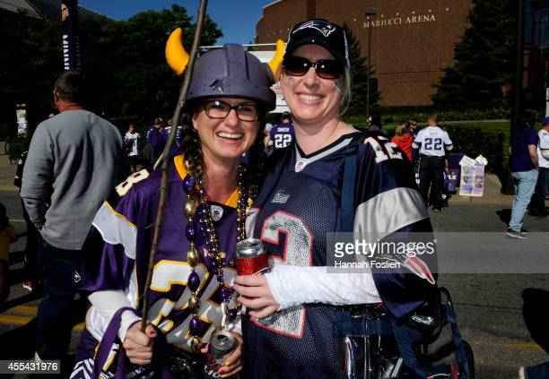A fan wearing the jersey of Adrian Peterson of the Minnesota Vikings carrying a switch and a fan of the New England Patriots pose for a portrait...