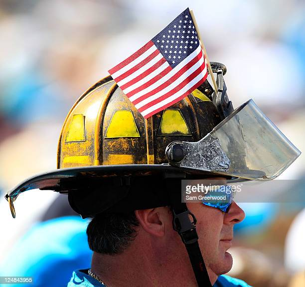 A fan wears a firemans helmet and American flag while watching the season opener game between the Jacksonville Jaguars and the Tennessee Titans at...