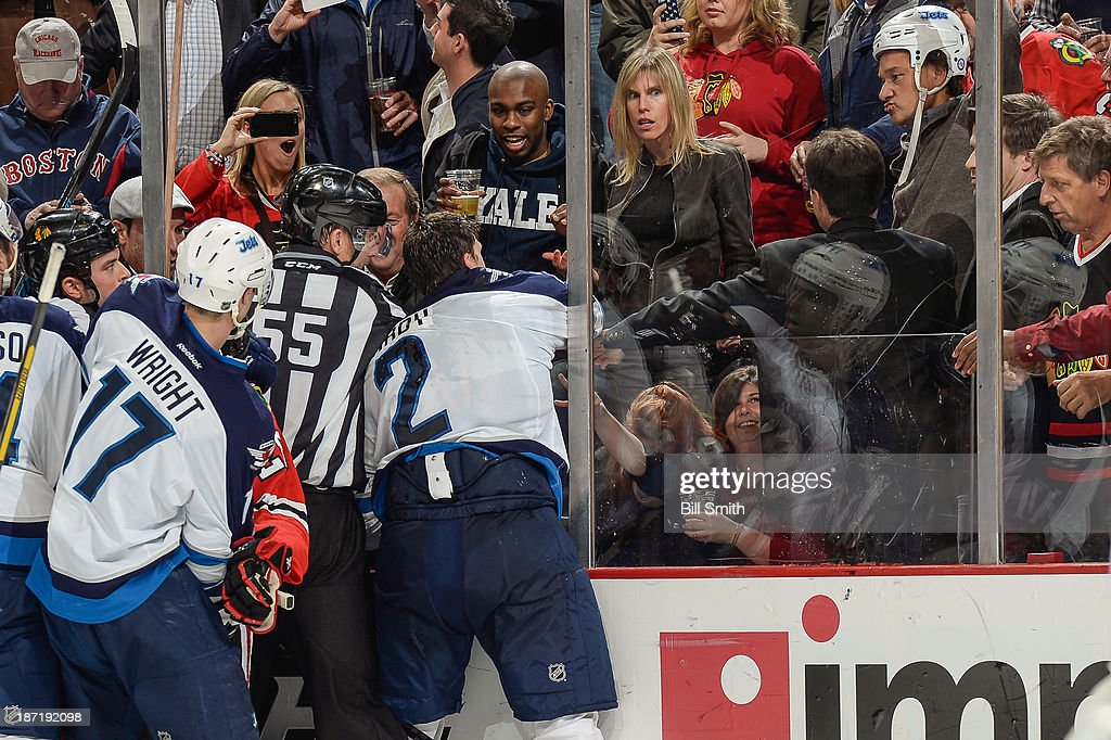 A fan wears a helmet ripped off the head of Adam Pardy #2 of the Winnipeg Jets, after the glass gave way due to a hard check to Pardy from Brandon Bollig #52 of the Chicago Blackhawks, during the NHL game on November 06, 2013 at the United Center in Chicago, Illinois.
