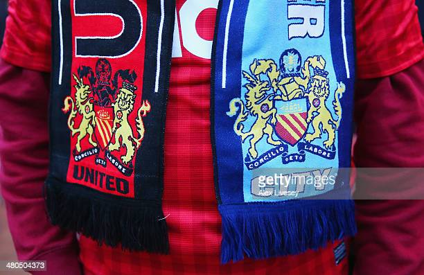 A fan wears a match scarf prior to the Barclays Premier League match between Manchester United and Manchester City at Old Trafford on March 25 2014...