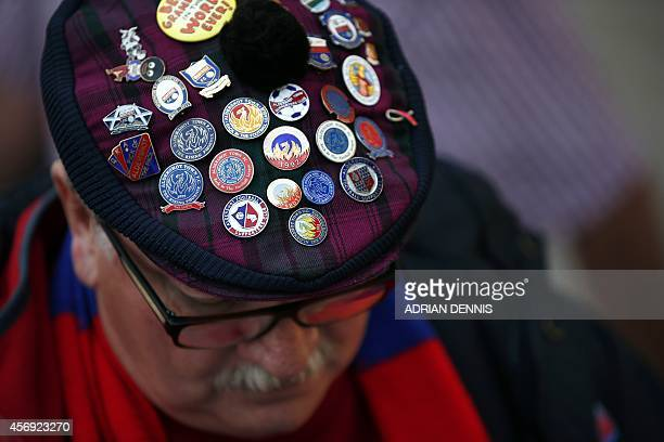 A fan wears Aldershot pins in his hat before the start of Vanarama Conference local derby football match between Aldershot and Woking at The...