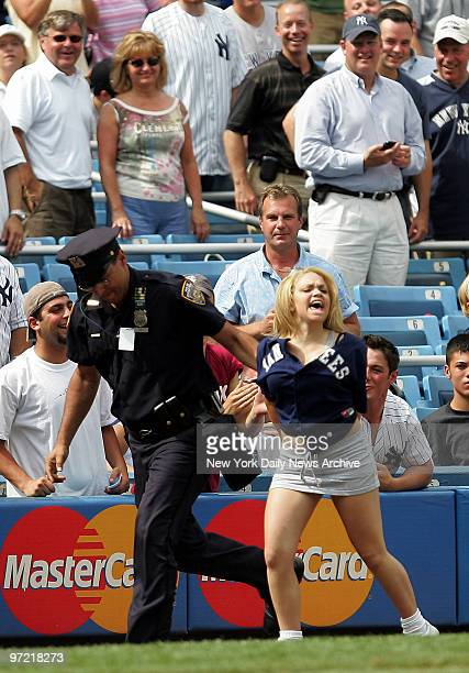 A fan who made her way onto the field is arrested during the 10th inning of a game between the New York Yankees and the Atlanta Braves at Yankee...