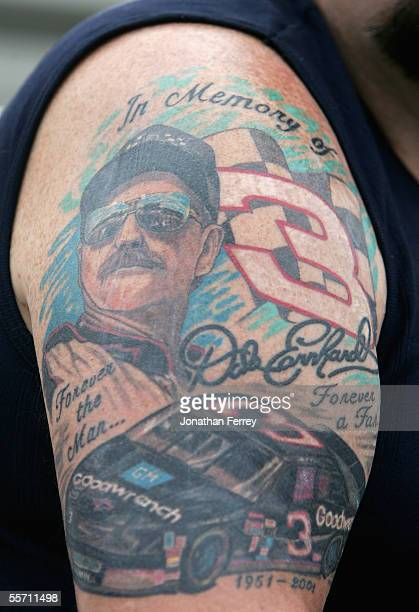 A fan with a Dale Earnhardt tattoo on his arm watches the qualifying for the NASCAR Nextel Cup Sylvania 300 on September 17 2005 at New Hampshire...