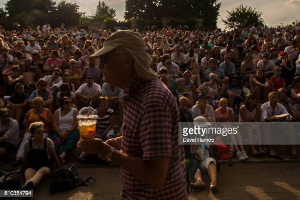 A fan with a galss of Pimm's walk past spectators look on from 'Murray Mound' on day five of the Wimbledon Lawn Tennis Championships at the All...