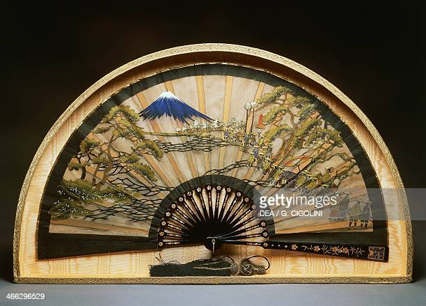 Fan with black lacquer slats and mother of pearl inlays decorated with a procession scene and Mount Fuji painted silk 57x30 cm Japanese civilisation...