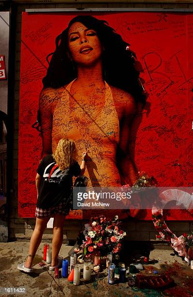 A fan writes a message on a billboard of the late singer and actress Aaliyah August 28 2001 on Sunset Boulevard in Hollywood CA Aaliyah and eight...