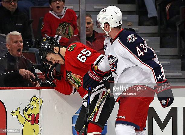 A fan yells as Andrew Shaw of the Chicago Blackhawks reacts after being hit by Scott Hartnell of the Columbus Blue Jackets at the United Center on...