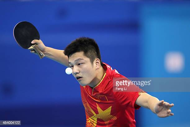 Fan Zhendong of China competes Yuto Muramatsu of Japan in table tennis Mixed International Team Gold Medal match during day seven of the Nanjing 2014...