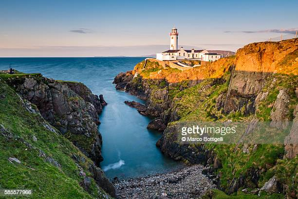 Fanad Head (Fánaid) lighthouse, County Donegal, Ulster region, Ireland, Europe. Lighthouse and its cove at sunset.