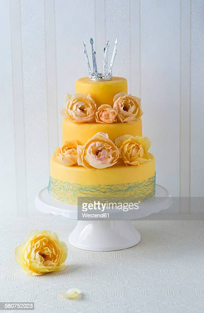 Fancy cake coated with fondant decorated with rose blossoms and little crown