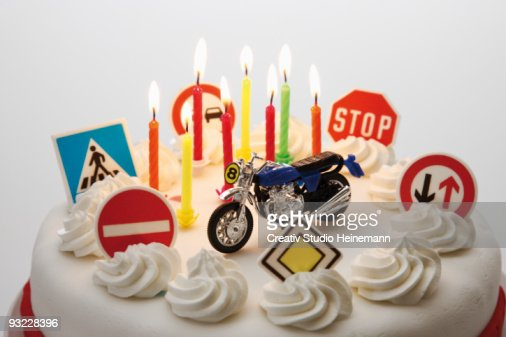 Fancy cake with road signs and toy motorbike, close-up