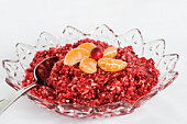 Cranberry relish made with fresh cranberries, oranges, and ginger in a pretty bowl on a white tablecloth.
