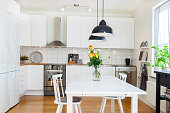 fancy modern kitchen interior with a bouquet of roses on the kitchen-table