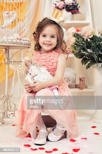 Modelo bonito Posando com Boneca em retro interior : Foto de stock