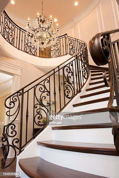 Fancy spiral staircase and traditional chandelier