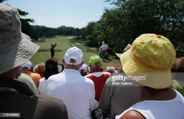 Fand watch as Larry Mize hits his tee shot on the first hole during the final round of the 2013 US Senior Open Championship at Omaha Country Club on...