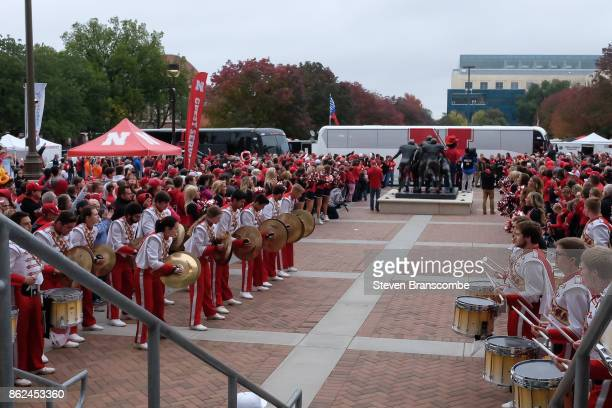 Fans and band members of the Nebraska Cornhuskers cheer on the arrival of the team before the game against the Ohio State Buckeyes at Memorial...