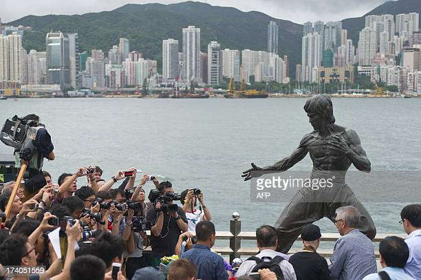 Fans and members of the media gather around a statue of Bruce Lee to mark the 40th anniversary of his death on the Avenue of the Stars in Hong Kong...