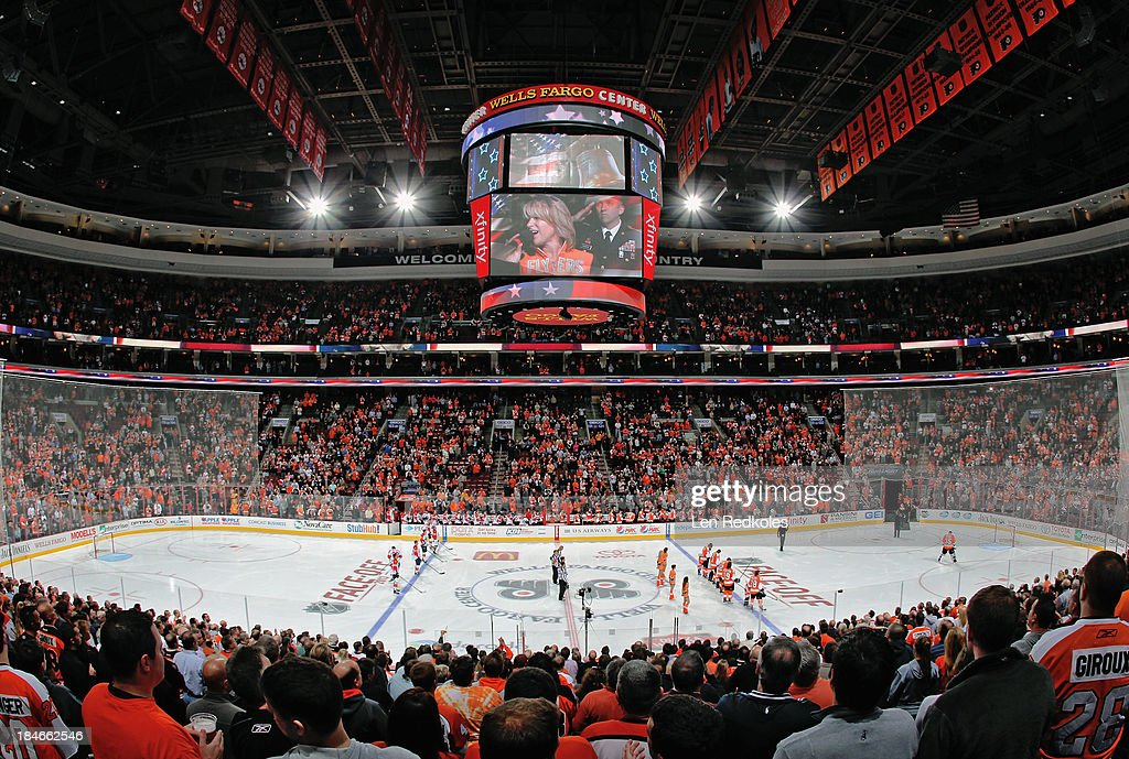 Fans and members of the Philadelphia Flyers and the Florida Panthers stand for the playing of the national anthem prior to an NHL game between the on...