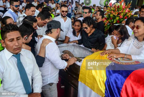 Fans and relatives of Colombian singer Martin Elias cry over the coffin during his funeral in Valledupar northern Colombia on April 16 2017 The...
