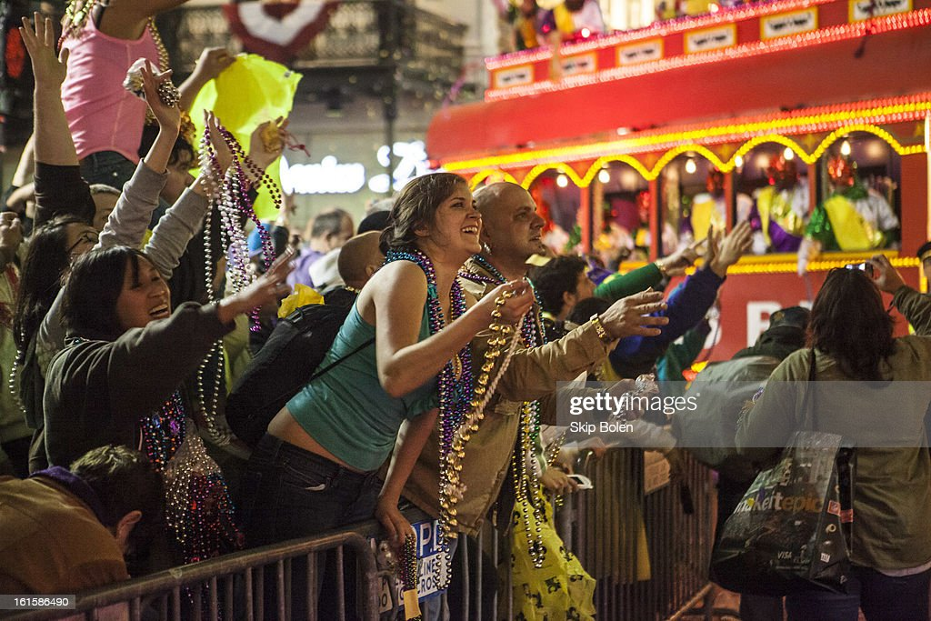 Fans and revelers catch beads tossed by the riders in the 2013 Krewe of Orpheus Mardi Gras Parade on February 11, 2013 in New Orleans, Louisiana.