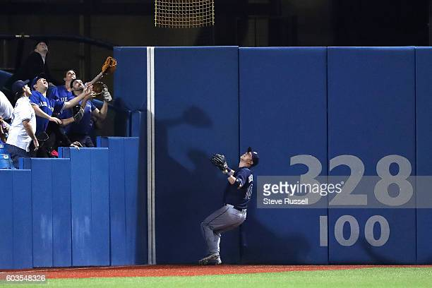 TORONTO ON SEPTEMBER 12 Fans and Tampa Bay Rays left fielder Mikie Mahtook watch as Ezequiel Carrera's hit approaches the wall Ezequiel Carrera hits...