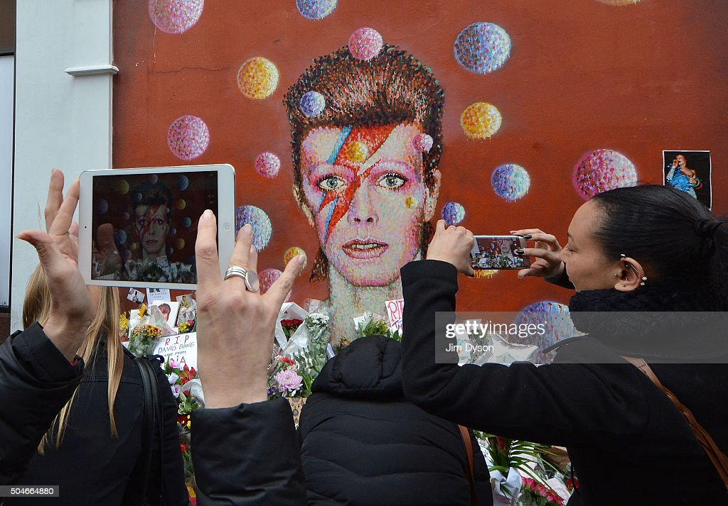 Fans and wellwishers gather to pay tribute to David Bowie at a mural in South London, on January 12, 2016 in London, England. British music and fashion icon David Bowie died yesterday at the age of 69 following an 18 month battle with cancer. The 'Aladdin Sane' mural has become something of an unofficial focal point for grieving fans as it is situated in his hometown of Brixton.