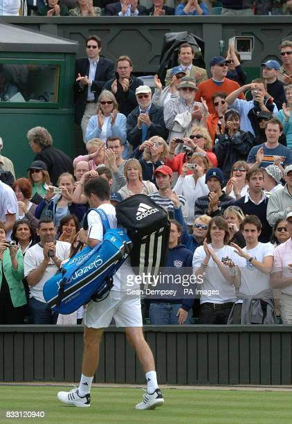 Fans applaud Great Britain's Tim Henman as he walks off following his defeat to Spain's Feliciano Lopez during The All England Lawn Tennis...