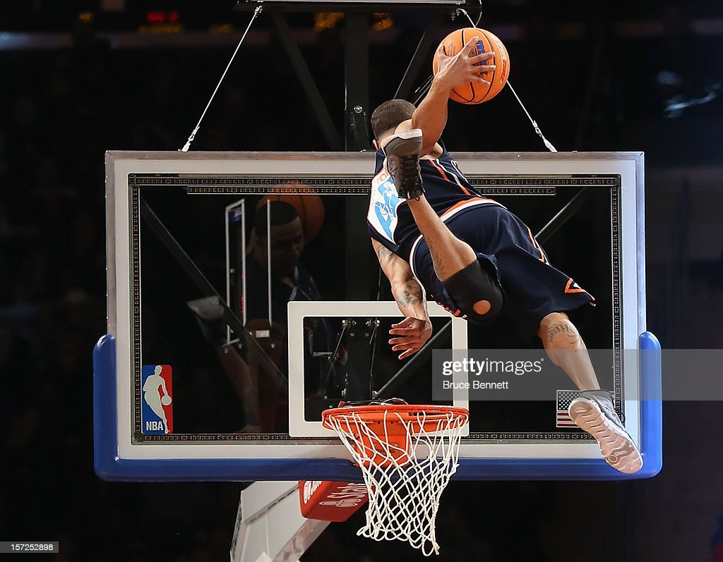Fans are entertained by athletes dunking basketballs at a break in the game between the New York Knicks and the Washington Wizards by stunt at Madison Square Garden on November 30, 2012 in New York City.
