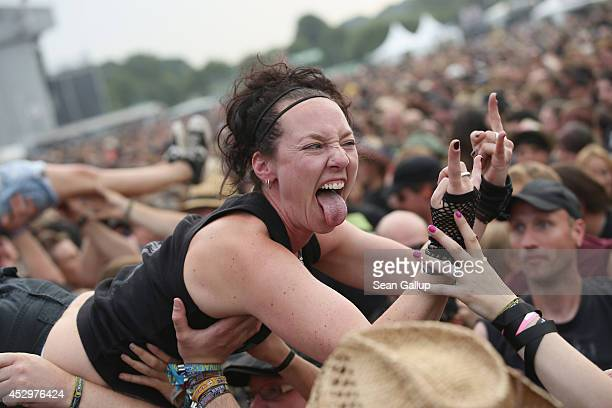 Fans are held up by fellow fans as they float towards the stage at the Hammerfall performance at the 2014 Wacken Open Air heavy metal music festival...