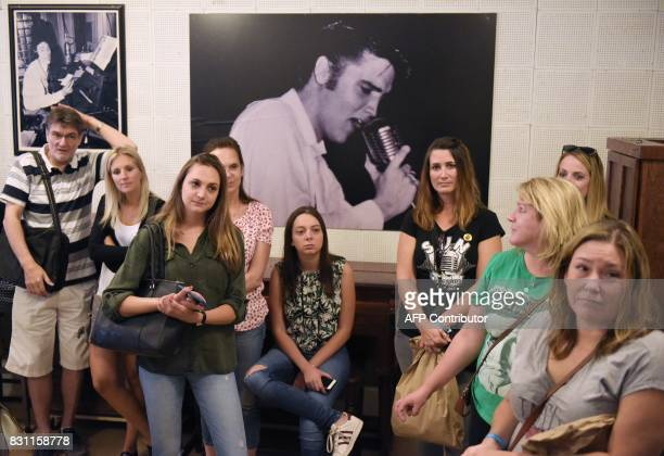Fans are seen in front of a photo of Elvis Presely during a tour of Sun Studio on August 13 2017 in Memphis Tennessee Forty years after his tragic...
