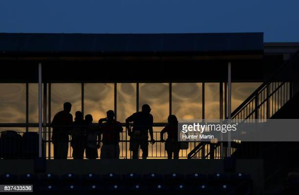 Fans are silhouetted as they watch the game from the upper level of the stadium in the ninth inning during a game between the Miami Marlins and the...